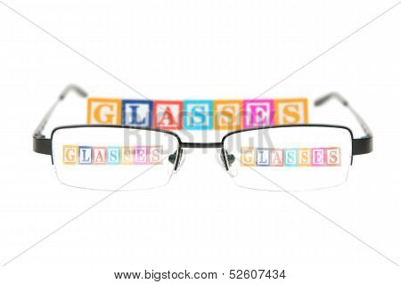 Letter Blocks Spelling Glasses With A Pair Of Glasses.