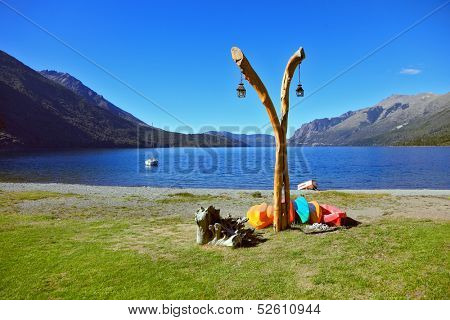 The original boathouse. Pole with lights and next to him on the ground dries colorful boats. The lake with the cold blue water and grassy bank