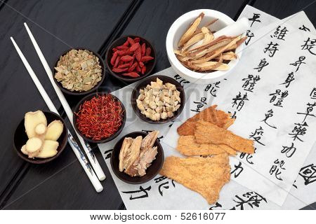 Traditional chinese herbal medicine selection with mandarin calligraphy on rice paper. Translation describes the medicinal functions to maintain body and spirit health and balance energy.