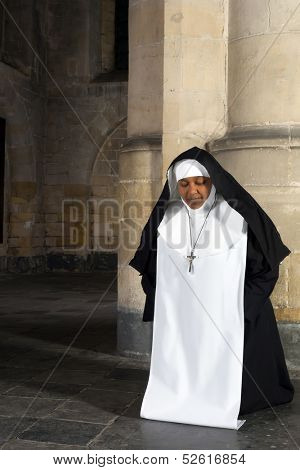 Nun kneeling in the medieval interior of a 14th century church in Belgium