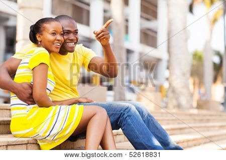happy african american couple sitting outdoors in the city