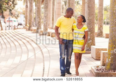 cheerful young afro american couple walking on urban street