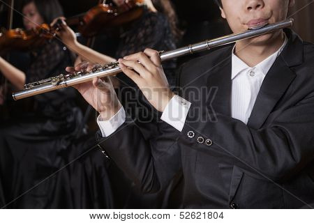 Flautist holding and playing the flute during a performance