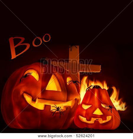Scary Halloween night, aggressive burning fire on graveyard near cross, glowing gourd with creepy spiders, copyspace with text, traditional autumn holiday of horror