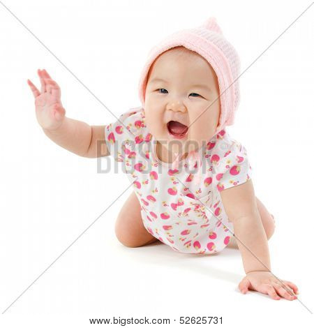 Six months old Asian baby girl crawling over white background, isolated.