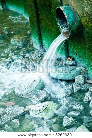 Some polluted water sewage or waste product gushing from a pipe into the river.