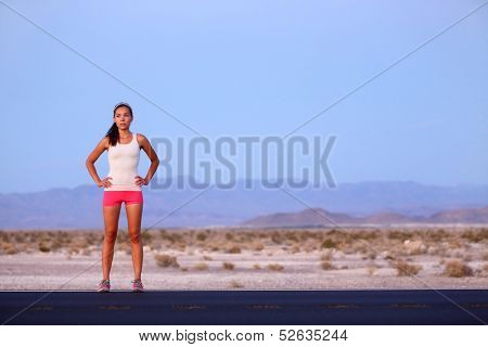 Athlete runner woman resting on road after running on highway in the USA. Beautiful fit fitness girl sweating and relaxing at dusk after a late night run. Mixed race Caucasian Asian female model, 20s.