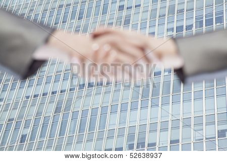 Close up of two businesspeople shaking hands by Chinas world trade center in Beijing
