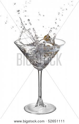 Martini with splash and olive isolated on white
