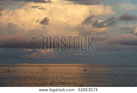 Beautiful sea view with the fishing boats and clouds formation in golden sunset hours, warm evening