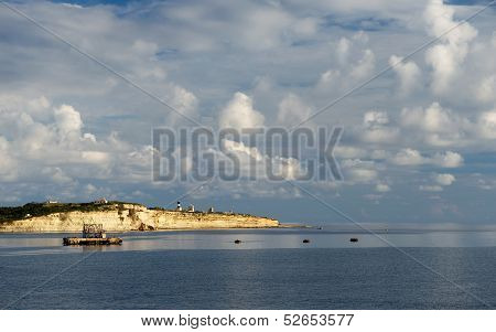 Beautiful sea view with the yellow rock and clouds formation in golden sunset hours, warm evening