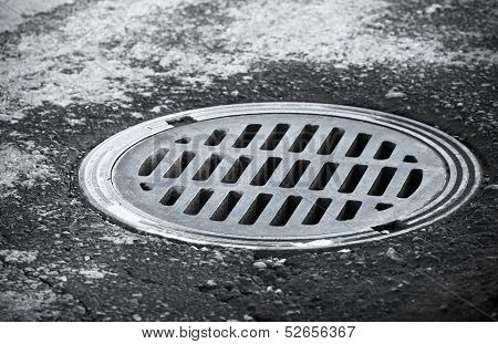 Sewer Manhole On The Urban Asphalt Road. Closeup Photo