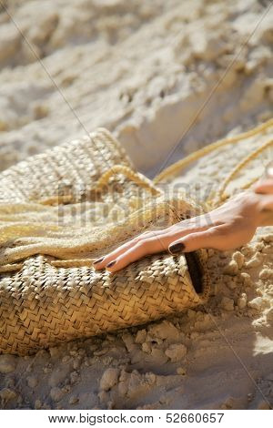 female handbag of straw on sand