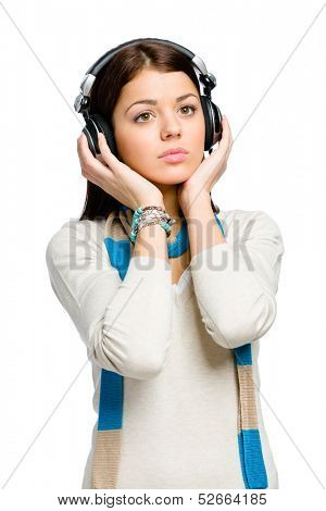 Half-length portrait of teenager listening to music in earphones, isolated on white
