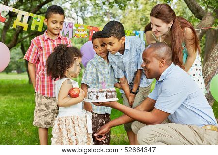Father gives birthday cake with burning candle on it to little daughter, family of five looks at it, happy birthday sign behind their backs