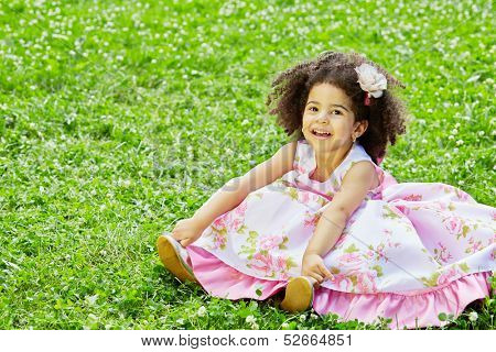 Little mulatto girl sits on grassy lawn spreading hem of her dress