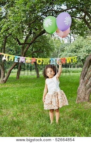 Little girl stands in park, holding three air balloons in her raised hand, happy birthday sign behind her back