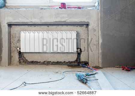 Construction apartment with an installed heating and a perforator on the floor