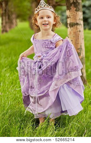 Little girl in beautiful violet gown and crown on head stands  on grassy lawn in park, lifting up slightly hem of gown