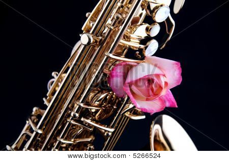 Gold Brass Saxophone And Pink Rose