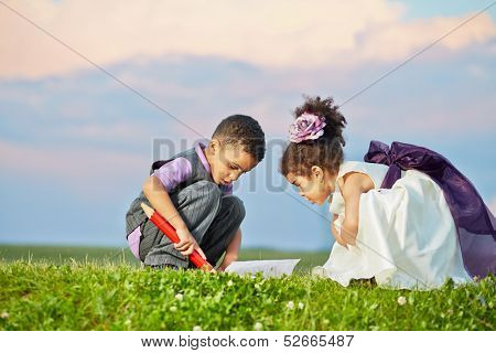 Little boy in grey suit and little girl in light gown with violet waistband sit squatted and examine open copybook that lies on grass