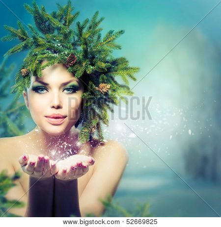 Winter Christmas Woman. Beautiful New Year and Christmas Holiday Girl Blowing Snow. Snowflakes. Hairstyle and Make up. Beauty Fashion Model Girl with Christmas Tree Hairstyle