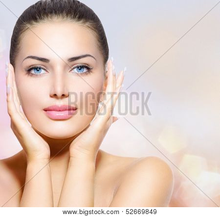 Beauty Portrait. Beautiful Spa Woman Touching her Face. Perfect Fresh Skin. Pure Beauty Model Girl. Youth and Skin Care Concept