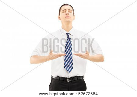 Young businessman meditating isolated against white background