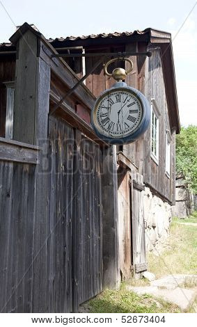 Wooden clock hangs above a street.
