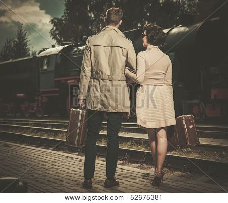 Beautiful vintage style couple with suitcases on  train station platform