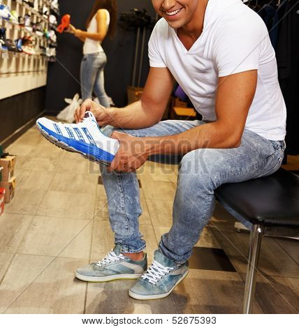Young handsome man choosing sport footwear in sport outlet