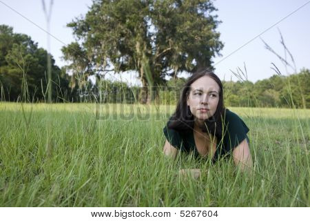 Thoughtful Girl Laying In Grass