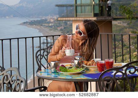 Young Woman Having Breakfast At Resort Restaurant Outdoor