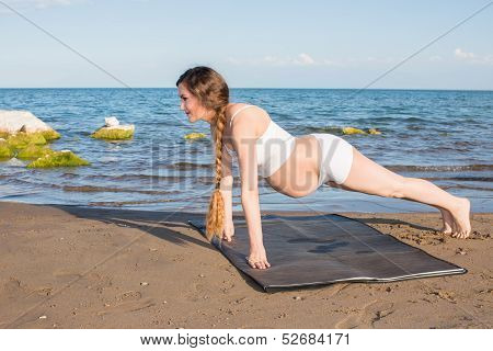 Healthy Pregnant Woman In Sports Bra Doing Exercise In Relaxation On Yoga Pose On Sea