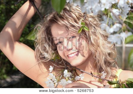 Beautiful Blond Woman Between Tree With White Flowers