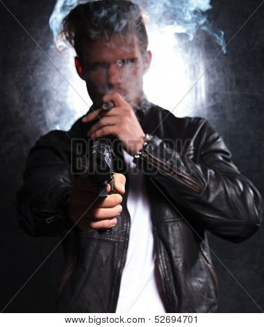 closeup picture of a young killer pointing his big gun at the camera and smoking a cigar