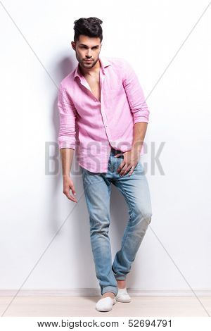 full length picture of a young fashion man posing with a hand at his crotch while looking into the camera. isolated on a white background