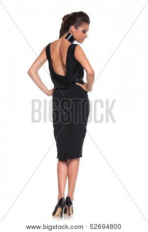 woman in a black dress with naked back on a white background - picture from behind
