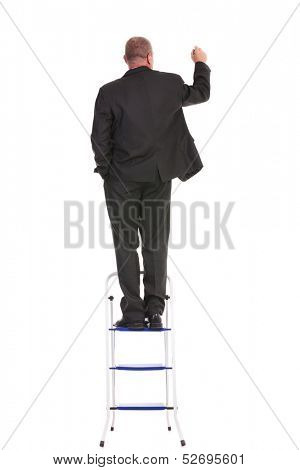 full length back view portrait of a business man standing on a ladder and writing on an imaginary screen while holding a hand in his pocket. on a white background
