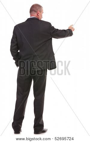 full length back view picture of a business man pushing an imaginary button while holding his other hand in his pocket. on a white background