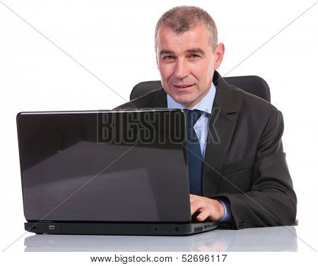 business man working on his laptop while looking into the camera. on a white background