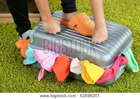 Suitcase with clothes on carpet on room background