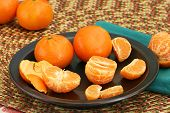stock photo of clementine-orange  - Whole and peeled clementines on a dark plate