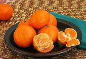 picture of clementine-orange  - Closeup of orange clementines on a dark plate