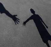 stock photo of tutor  - Helping Hand with a shadow on pavement of an adult hand offering help or therapy to a child in need as an education concept of charity towards needy kids and teacher guidance to students who need tutoring - JPG
