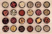 foto of licorice  - Traditional chinese herbal medicine in wooden bowls over papyrus background - JPG