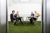 Four people meeting in a green, sustainable, conference room