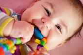 picture of teething baby  - Smiling and playing baby with teething ring - JPG