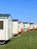 image of trailer park  - Scenic view of row of caravans in trailer park with blue sky background - JPG