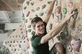stock photo of climbing wall  - Smiling young man climbing up a climbing wall - JPG